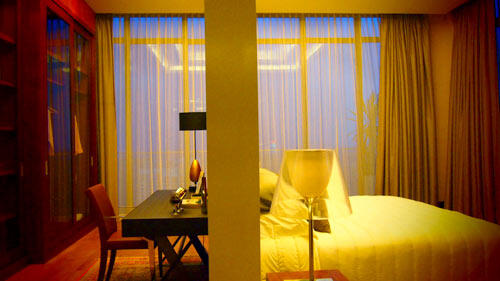 in the master bedroom there is a study area behind the bed